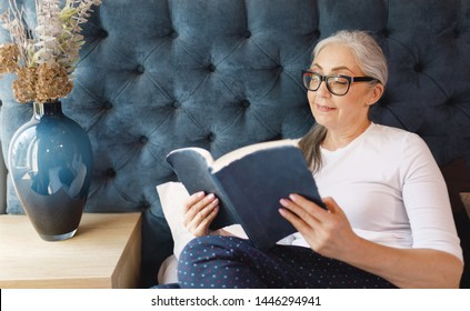 Pretty old woman with grey hair in eyeglasses reading book in bedroom