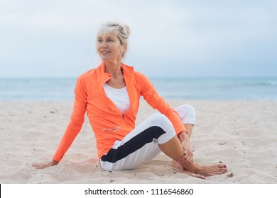 Pretty older blond woman relaxing on a beach in sportswear turning to look back over her shoulder watching something