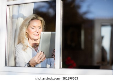 Pretty older blond woman sitting at the window with her tablet and relaxing in the sun