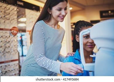 Pretty optometrist helps a smiling black woman sit at a machine and take her eye exam