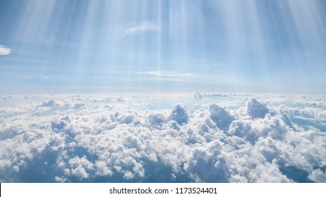 Pretty panorama of a cloudscape a landscape of clouds and sunbeams seen from above from an airplane window