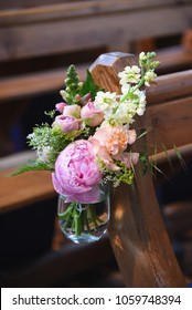 Pretty pastel church flowers hanging on a pew for a wedding