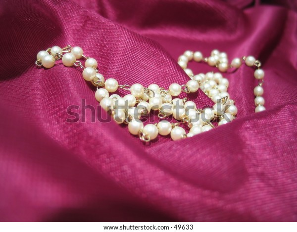 Pretty pearl necklace on dusty rose satin-like material.