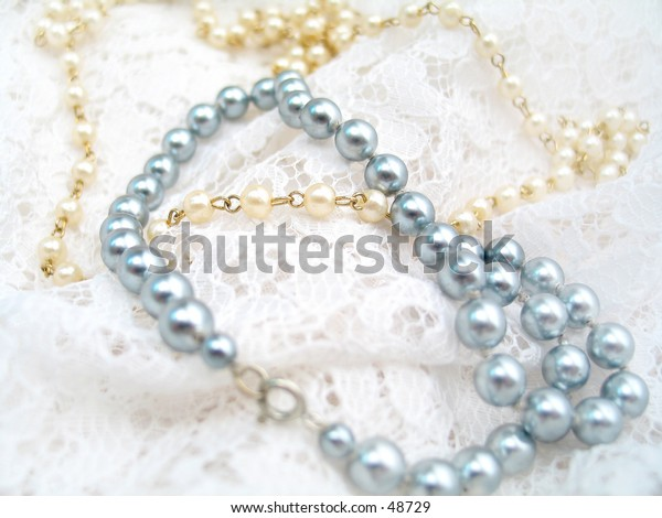 Pretty pearl necklaces on white lace material.
