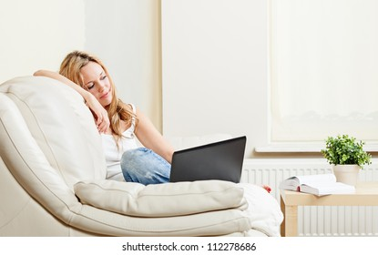 Pretty pensive young woman sitting on white couch with laptop computer