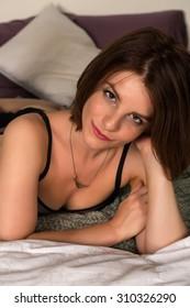 Pretty petite brunette in bed in black lingerie