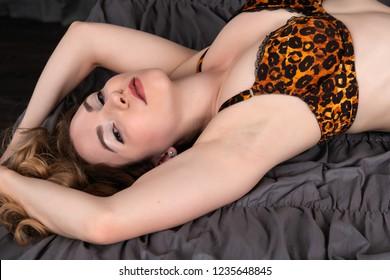 Pretty petite brunette dressed in vintage leopard print lingerie
