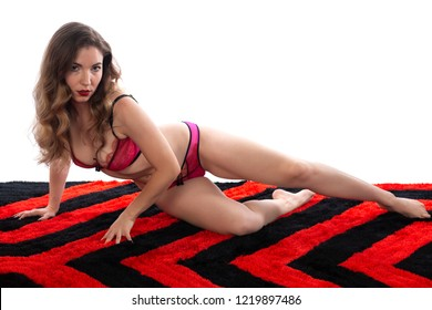 Pretty petite brunette in pink and purple lingerie on a red and black rug