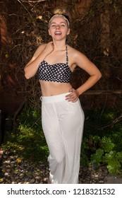 Pretty petite brunette in a polka dot midriff top and white slacks