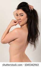 Pretty petite brunette standing nude on gray