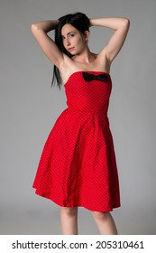 Pretty petite young woman in a red dress