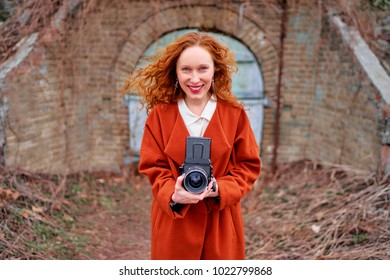Pretty photographer. Long hair young woman with old fashioned camera taking pictures outdoors