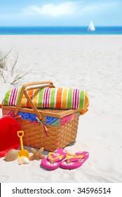 Pretty picnic basket and beach supplies at seashore