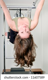 Pretty Pilates Instructor Hanging Upside Down from Trapeze Table