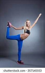 Pretty pilates instructor posing in studio