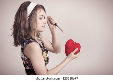 Pretty pin up woman cutting a toy heart with a knife