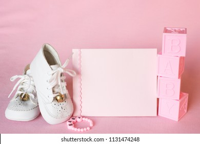 Pretty Pink Baby Girl Shower Invitation Card or Birth Announcement with vintage white shoes on Pink Cloth Background with room or space for copy, text, or your words. Horizontal photo with a side view