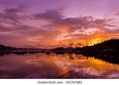 Pretty Pink orange Sky cloudscape over an island with reflection at Sunset on the Island of Coron, Palawan, Philippines