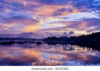 Pretty Pink orange Sky cloudscape over an island with reflection and wooden traditional filipino boats at Sunset on the Island of Coron, Palawan, Philippines