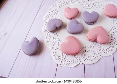 Pretty pink and purple heart shaped French macaron cookies.