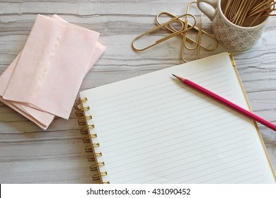 Pretty pink stationary, pencil and gold paperclips with blank notebook page over head view with room for copy.