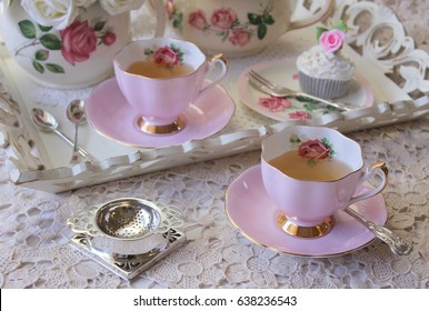 Pretty pink vintage afternoon tea party, tea cups, teapot, cup cake and silver cutlery flatware on wooden tray and lace tablecloth