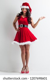 Pretty Pin-up style Santa girl in red hat holding something , white background