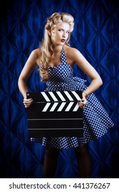 Pretty pin-up woman with retro hairstyle and make-up posing with clapper board over vintage background.