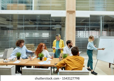 Pretty pleased people dressed in casual clothes, sit at big table with different work devices, longs for knowledge, looks away, express interest, work process concept