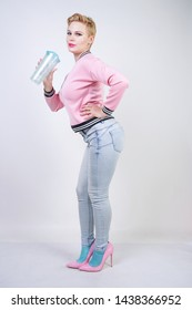 pretty plus size short hair woman with blue cup of water. blonde adult girl wearing sport pink jacket and jeans posing on white studio background alone.