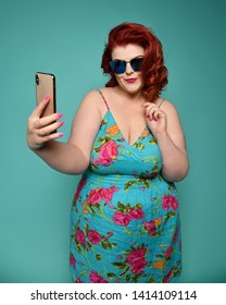 Pretty plus-size fat woman in fashion sunglasses and colorful clothes does fashion selfie like she is nice and shy girl on mint background