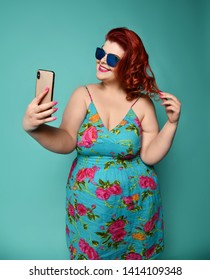 Pretty plus-size fat woman with hollywood smile in fashion sunglasses and colorful clothes does fashion selfie with pursed lips on mint background