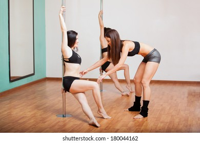 Pretty pole fitness instructor assisting one of her students during class
