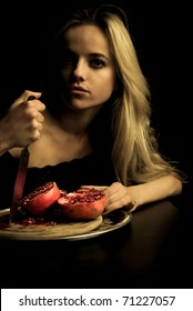 Pretty pomegranate killer. Girl holding knife in hand near cutted bloody fruit.