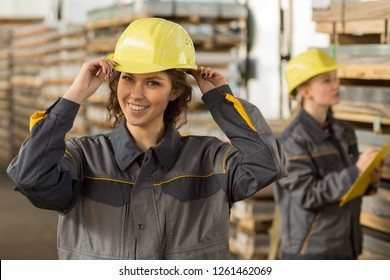 Pretty and positive girls working at metal base, holding on head yellow helmet with two hand, smiling at camera. Second worker checking shelves with yellow clipboard in hand. Concept of industry.