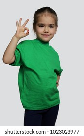 Pretty preschool girl in green t-shirt showing ok sign over white background, beauty and fashion concept