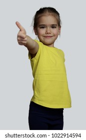 Pretty preschool girl in yellow t-shirt making the ok sign over white background, beauty and fashion concept