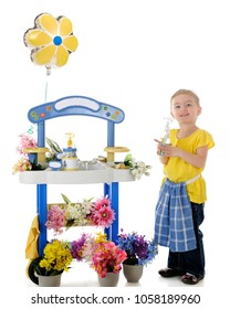 A pretty preschooler standing happily with a spray bottle by her flower stand.  On a white background.