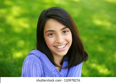 pretty preteen ethnic girl sitting in grass