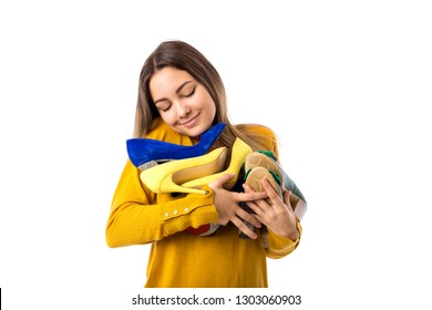 Pretty proud young woman holding many shoes over white background