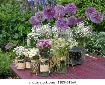 Pretty purple and white flowers in jars ready to decorate the table