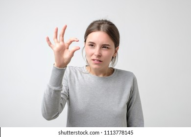 Pretty puzzled girl shows something invisible with her fingers. Small amount of important object