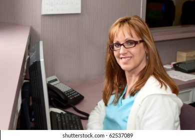 Pretty receptionist in doctor's office sitting in front of computer