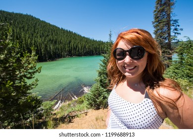 Pretty red hair female adult poses by Sparks Lake along the Cascade Lakes Scenic Byway near Bend, Oregon. Water is teal