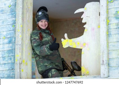 Pretty red hair girl in paintball mask showing thumb up