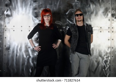 Pretty red hair girl and young man pose together near metal wall in studio