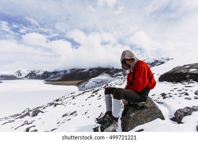 Pretty, red haired, european girl standing on the trail surrounded by stones, snow and ice in Himalaya mountains. Tilicho lake.