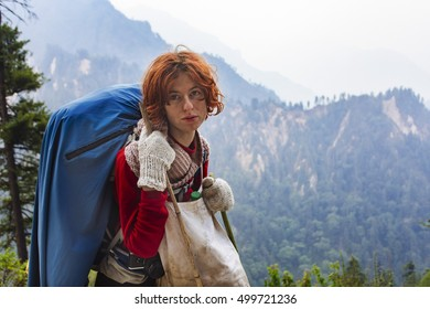 Pretty, red haired, european girl standing in the Himalaya mountains, Nepal.