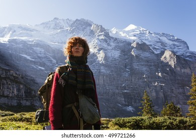 Pretty, red haired, european girl, dressed in red sweater, black leggings and a pair of braces, standing on the path in the swiss Alps with the backpack on her back, Switzerland.