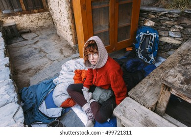 Pretty, red haired, european girl sitting and eating breakfast in Himalaya mountains, Nepal.